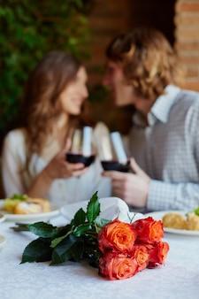 Primer plano de un ramo de flores con una pareja bebiendo vino