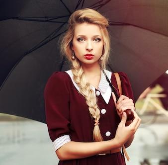 Primer plano de una mujer joven rubia sosteniendo un paraguas