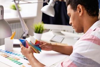 Primer plano manos de un estudiante eligiendo un color