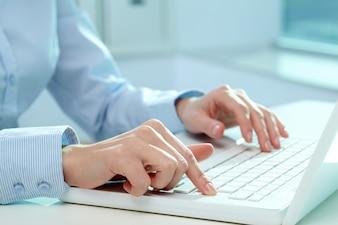 Primer plano manos de una empresaria escribiendo en el teclado