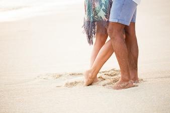 Primer plano, pareja, piernas, arena