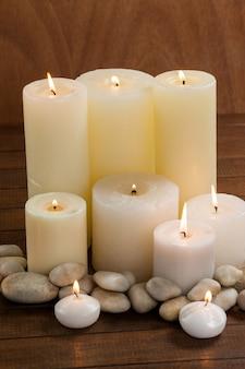 Primeros planos de velas blancas y guijarros de piedra en la madera