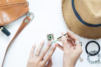 Proceso de manicura. El esmalte de uñas que se aplica a la mano, el esmalte es de color verde. Mujer accesorios sobre fondo blanco