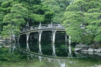 Puente de piedra sobre el estanque en el patio