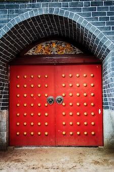 Puerta roja con decoración de botones dorados