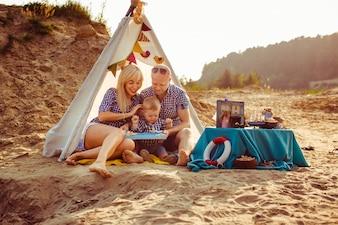 """Familia sentado en la arena bajo carpa"""