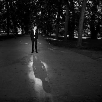 """""""Hombre en traje de pie en el parque"""""""