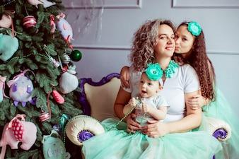 """""""Madre sentada con hijas sonriendo abrazos"""""""
