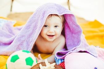 """""""Niño pequeño tendido cubierto con una toalla de color púrpura"""""""