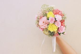 Ramo de flor en mano y pared blanca con efecto de filtro retro
