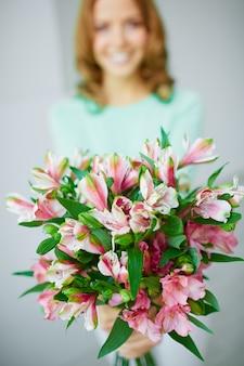 Ramo de flores con mujer borrosa de fondo
