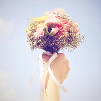 Ramo de flores en la mano y cielo azul con efecto de filtro retro