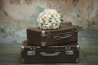 Ramo de flores sobre unas maletas de viajes