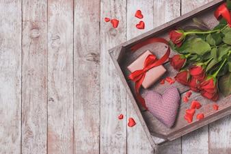 Ramo de rosas en una bandeja con un corazón y un regalo