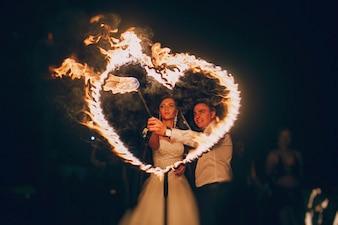 Recién casados encendiendo un corazón de fuego