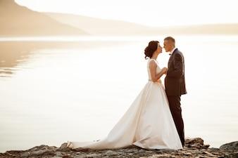 Recién casados mirándose a los ojos en un lago