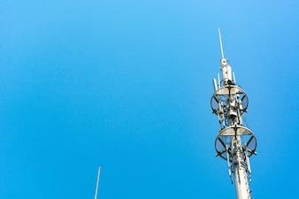 Red y blanco torre de comunicaciones con un montón de diferentes antenas bajo el cielo azul y las nubes