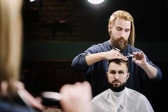 Reflejo del peluquero cortando el cabello del hombre ante el espejo