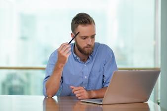 Reflexivo de mediana edad Hombre que trabaja en la computadora portátil