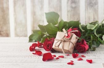 Regalo marrón apoyado en rosas