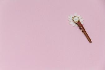 Reloj y pétalos sobre fondo rosa