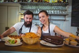 Retrato de camarero y camarera coloca en el contador