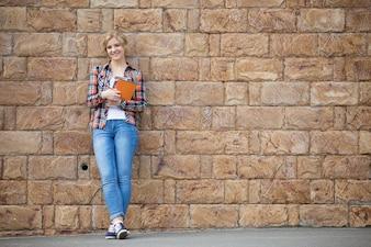 Retrato de cuerpo entero de la muchacha del estudiante contra la pared de ladrillo con los libros de texto
