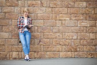 Retrato de cuerpo entero de una chica estudiante contra la pared de ladrillo