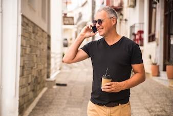 Retrato de hombre guapo beber café y hablar hablando por teléfono