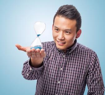 Retrato de hombre joven asiático hermoso que sostiene un reloj de arena
