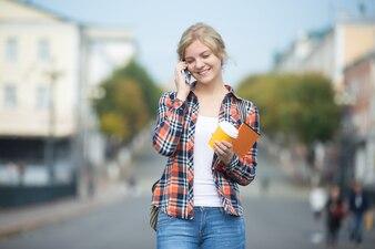 Retrato de joven en contra de la calle borrosa, hablando por teléfono