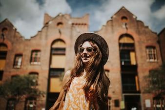 Retrato de la muchacha sonriente linda en gafas de sol con los edificios de la ciudad en el fondo.