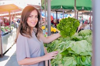 Retrato de mujer joven hermosa que elige verduras de hoja verde en mercado verde. Concepto de compras de alimentos saludables. Joven comprar verduras en el mercado verde.