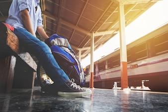 Retrato de un joven viajero esperando tren y bolsa de viaje