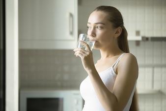 Retrato de una muchacha atractiva joven que bebe el agua