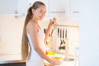 Retrato de una mujer joven degustación de una ensalada verde en la cocina,