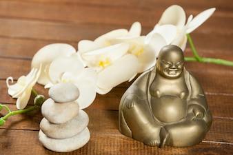 Riendo figurilla de Buda con los guijarros de piedra y la flor