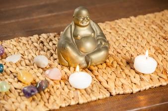Riendo figurilla de Buda, piedra piedras y velas encendidas