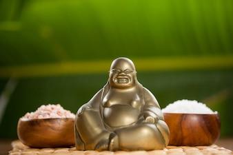Riendo figurilla de Buda y la sal del mar en un tazón de madera