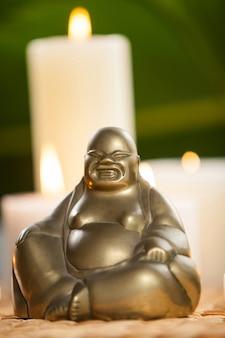 Riendo figurilla de Buda y velas encendidas en la estera