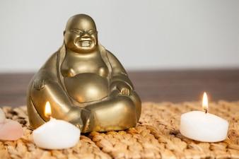 Riendo figurilla de Buda y velas encendidas