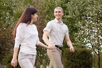 Riendo pareja caminando en el parque
