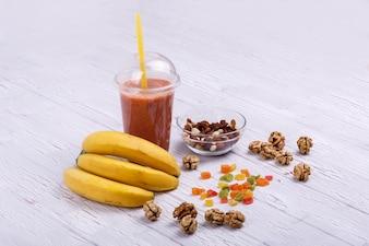 Rojo detox coctail con plátanos en frutas confitadas se encuentra en la mesa blanca