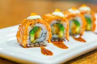 Rollos de sushi japonés con salmón fresco crudo en un plato blanco.