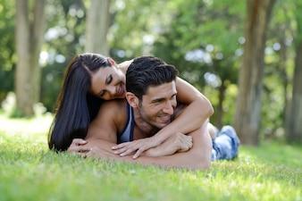 Romántica pareja abrazándose en el césped