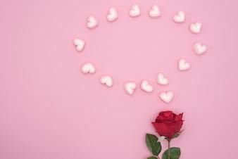 Rosa roja con corazones de discurso de burbuja sobre fondo de papel de color rosa
