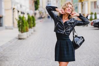 Rubia chica posando de pie en la calle