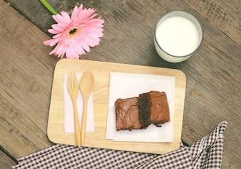 Sabrosas brownies con vaso de leche y flores