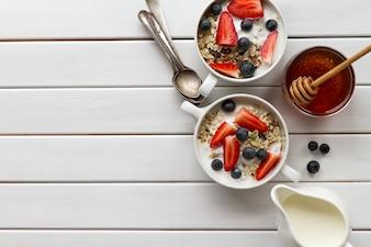 Sabroso desayuno colorido con harina de avena, yogur, fresa, arándano, miel y leche en blanco Fondo de madera con espacio de copia. Vista superior.