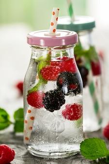 Saludable sabrosa agua fresca de desintoxicación refrescante en botellas o frascos con frambuesa, mora, menta y hielo sobre fondo de madera. De cerca. Concepto De Vida Saludable.